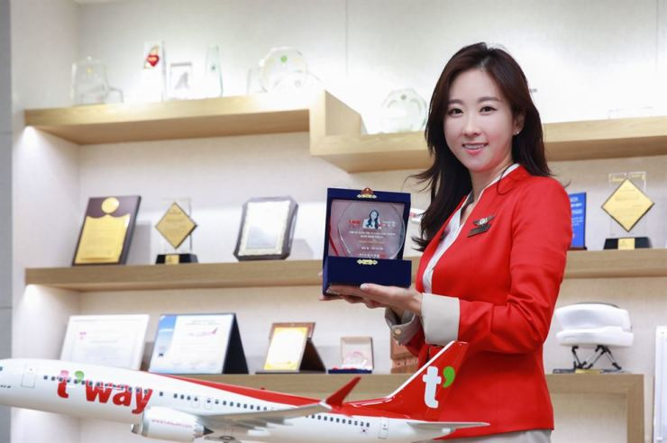 Nam Kyun-ah, a T'way Air flight attendant, holds her 5,000 flight hour award at the low cost carrier's headquarters in Seoul, July 23. Courtesy of T'way Air