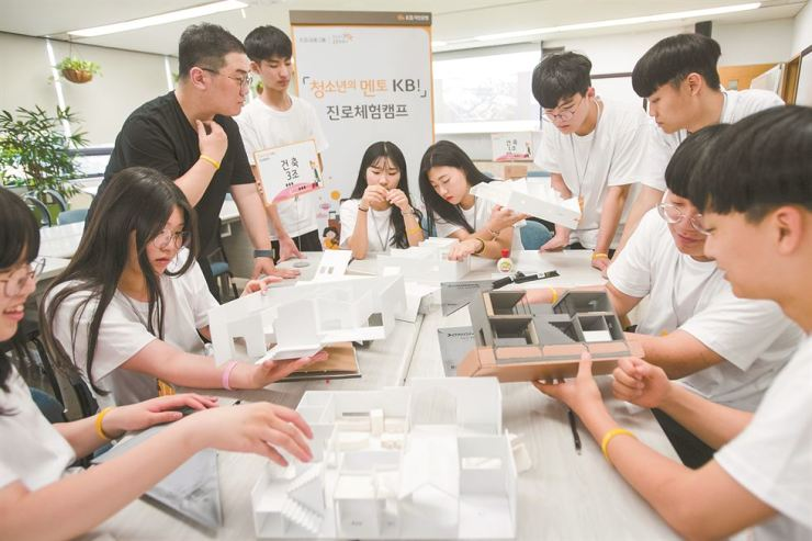 High school students build model houses at a summer camp hosted by KB Kookmin Bank at the bank's training center in Cheonan, South Chungcheong Province, Thursday. The bank invited some 130 students interested in the construction, digital and music sectors.