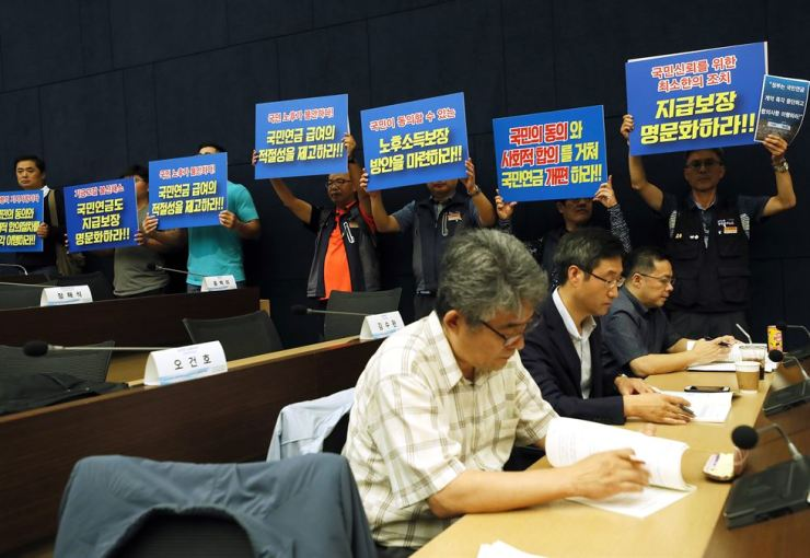 Members of a civic group hold a protest at the Korea Chamber of Commerce and Industry in Seoul, Friday, calling on the National Pension Service to secure their post-retirement pension. Yonhap