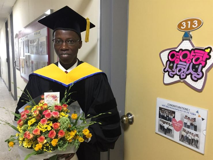 Didace Ndahimana from Rwanda holds a bouquet in front of his laboratory at Gangneung-Wonju National University (GWNU) in Gangneung, Gangwon Province, Wednesday, after receiving a doctor of science degree from the university. / Courtesy of GWNU