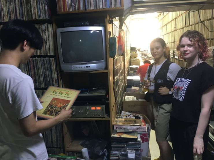 DJ Bowlcut and two Mutzine x Makers participants dig for vinyl records at Dol Record near Dongmyo Station during the Makers field trip. / Courtesy of Mutzine x Makers