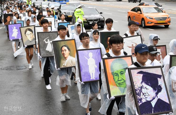 Student activists walk in Gwanghwamun Square, Seoul, holding the portraits of 293 female independence fighters to raise public awareness of these forgotten heroes in this Aug. 14, 2017, file photo. / Korea Times file