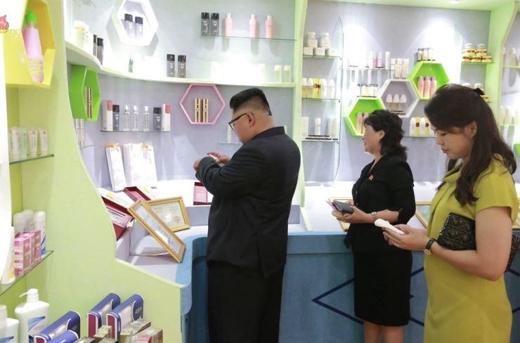 North Korean leader Kim Jong-un and his wife Ri Sol-ju, right, visit the Sinuiju Cosmetics Factory in North Pyongan Province on July 1. Yonhap