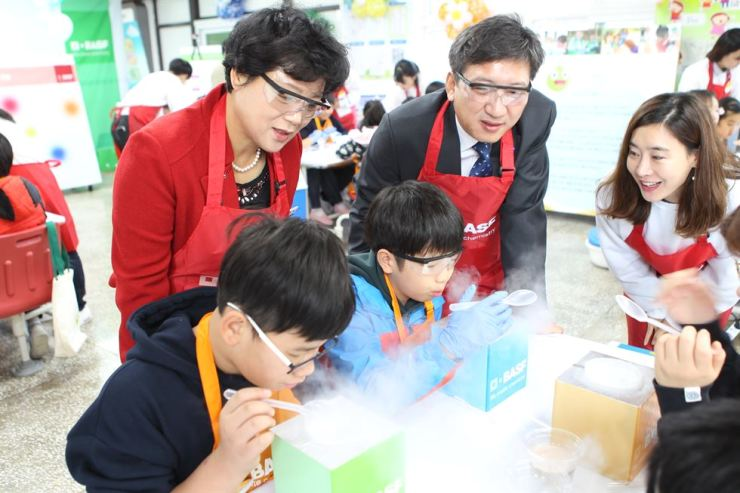 Jeon Sung-hyun, right, a manager at the corporate affairs team of BASF Korea, helps children conduct a safe experiment during the company's Kids' Lab program held at the Dooseo Elementary School in Ulsan, Nov.29, while Park Young-ok, left, vice-principal of the school, and Yoo Sung-jung, BASF Ulsan site manager, look on. / Courtesy of BASF Korea