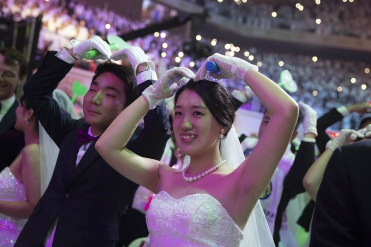 A couple raises their hands to make a heart during the Unification Church's mass wedding ceremony at Cheongshim Peace World Centre in Gapyeong, South Korea, on Monday. / Korea Times photo by Choi Won-suk