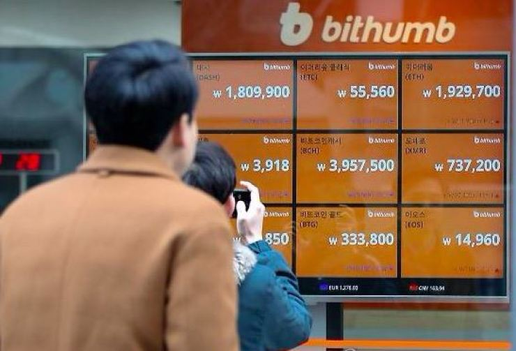 Virtual coin investors watch a display board at the Bithumb crypto exchange in Seoul. / Yonhap