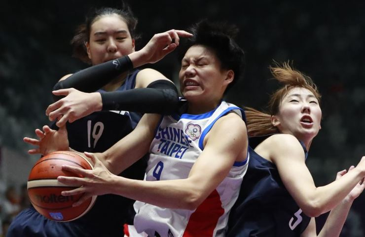 Taiwan's Huang Pingjen, center, battles for the ball with combined Koreas' Park Jisu, left, and Park Hyejin during their women's basketball semifinal match at the 18th Asian at Istora Stadium in Jakarta, Indonesia, Thursday, Aug. 30, 2018. AP-Yonhap