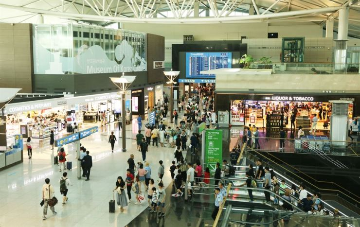 Travelers shop at duty free stores in Incheon International Airport's first passenger terminal in this file photo. Retail giants and air carriers said they are concerned about the government's attempt to open arrival duty free shops. / Courtesy of Incheon International Airport Corp.