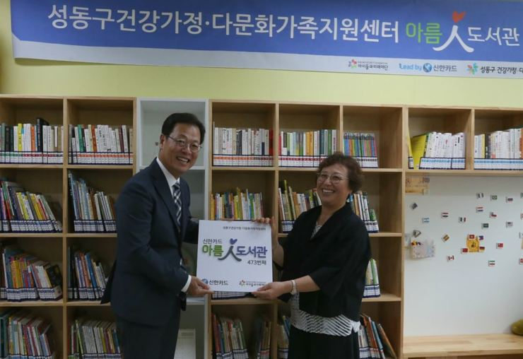 Shinhan Card Deputy President Choi In-seon, left, holds a signboard for a new library opened in a welfare center for multiracial families in Seongdong-gu, Seoul, Monday. The card firm has been financially supporting welfare centers to open libraries since 2010. Courtesy of Shinhan Card
