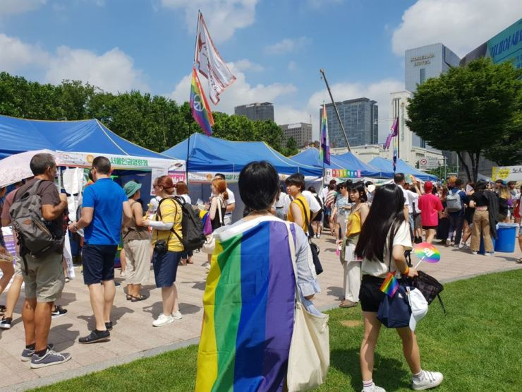 A participant with a rainbow flag explores the 19th Seoul Queer Culture Festival held at Seoul Square on July 14. / Korea Times photo by Lee Suh-yoon