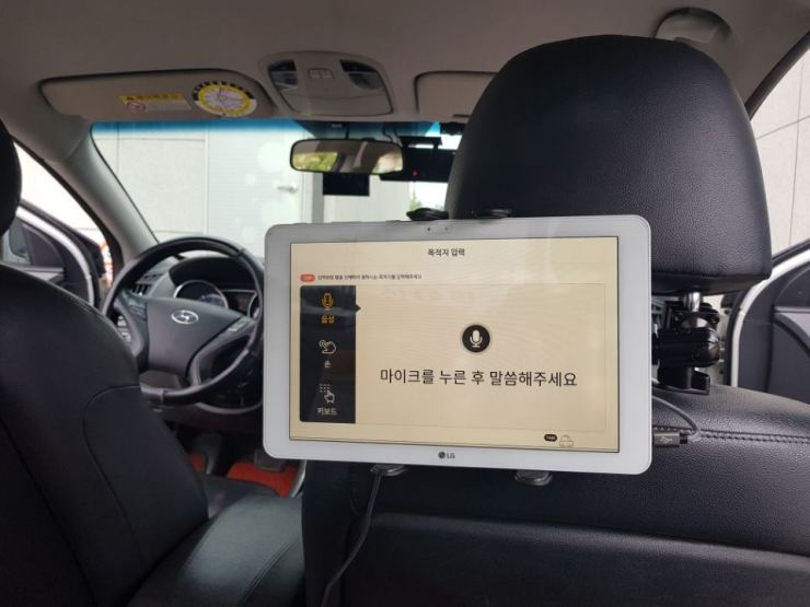 A tablet PC set up inside a taxi features the 'Goyohan Taxi' app to facilitate communication between deaf drivers and their passengers. / Courtesy of Coactus