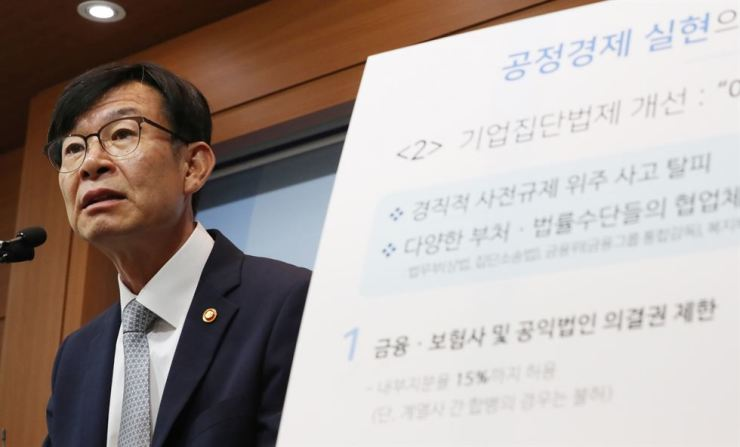 Fair Trade Commission Chairman Kim Sang-jo explains to reporters the latest proposed revision to a law regulating family-run conglomerates' business transactions with their subsidiaries and affiliates at the Sejong Government Complex, Sunday. Yonhap