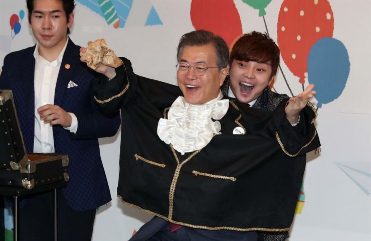 President Moon Jae-in helps magician Choi Hyun-woo at a daycare center in Seoul in January. Korea Times file