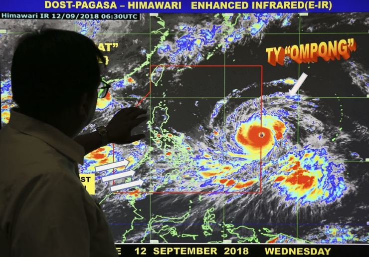 Filipino forecaster Meno Mendoza shows the path of Typhoon Mangkhut, locally named 'Typhoon Ompong' as it approaches the Philippines with sustained winds of 205 kilometers per hour (127 miles per hour) and gusts of up to 255 kph (158 mph), at the Philippine Atmospheric, Geophysical and Astronomical Services Administration in metropolitan Manila, Philippines on Wednesday, Sept. 12, 2018. Philippine officials say they plan to evacuate thousands of villagers, shut down schools and offices and scramble to harvest rice and corn as the most powerful typhoon so far this year menacingly roars toward the country's north. AP-Yonhap
