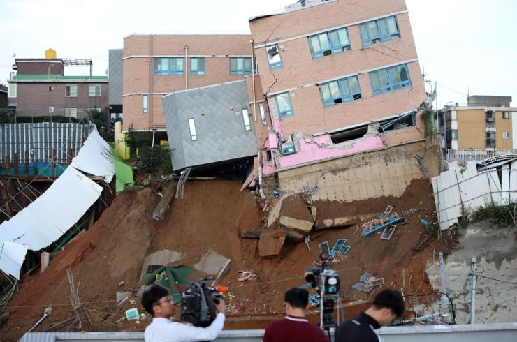 The building of Sangdo Kindergarten in Dongjak-gu, Seoul, hangs precariously over the edge, Friday, after its partial collapse the previous night. / Yonhap