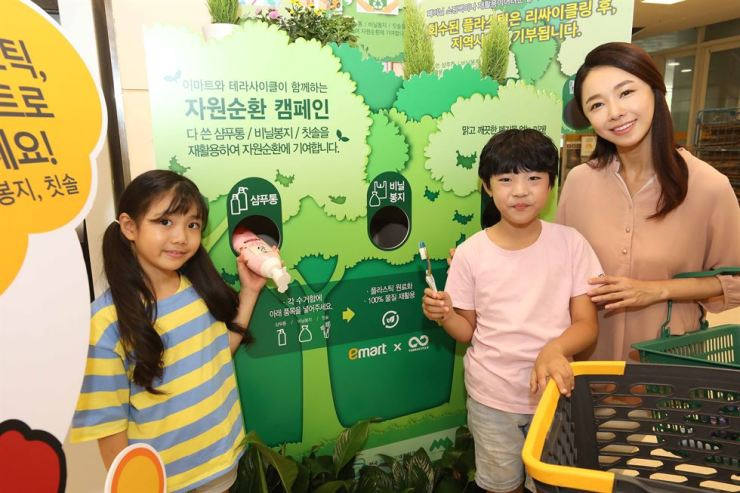 Children put a used shampoo bottle and a toothbrush in a plastic recycling bin at an E-mart store in Seongsu, Seoul, Thursday. The discount chain said TerraCycle, a global recycling company, will make children's chairs and various other products with the plastic and then donate them to the local community. / Courtesy of E-mart