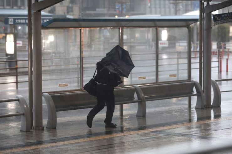A man struggles to hold his umbrella against strong wind and rain in Kagoshima, on Kyushu island, on September 30, 2018. AFP