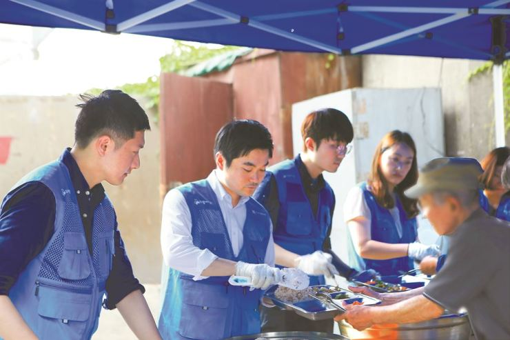 Export-Import Bank of Korea employees volunteer to serve meals for the underprivileged at a homeless center near Yeongdeungpo Station in Seoul. / Courtesy of Export-Import Bank of Korea