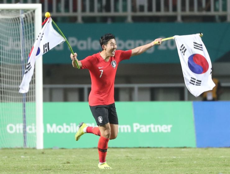 South Korea's Son Heung-min celebrates with Korean national flags after winning Japan during the soccer men's gold medal match at the 2018 Asian Games in Bogor, Indonesia, Saturday. South Korea won 2-1. Yonhap