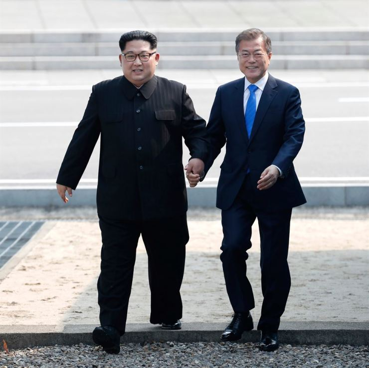 In this April 27, 2018 file photo, North Korean leader Kim Jong Un, left, and South Korean President Moon Jae-in cross the military demarcation line to the South side at the border village of Panmunjom in the Demilitarized Zone, South Korea. Korea Times file