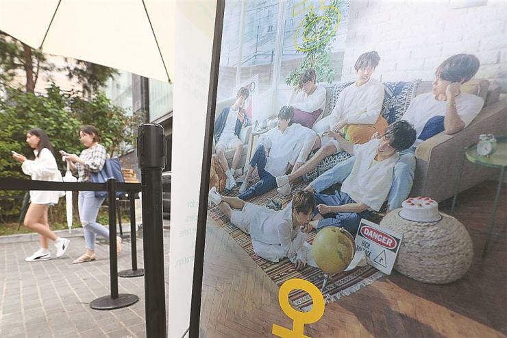 Visitors at the '2018 BTS Exhibition (Five, Always),' marking the group'fifth anniversary, walk beside a large promotional photo of the seven-member K-pop boy band at ARA Art Center in Jongno-gu, Seoul, Monday. The exhibition showcases previously unseen photos of BTS members until Oct. 28. / Yonhap