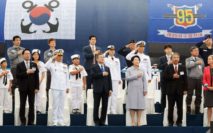 President Moon Jae-in, front row third from left, salutes while participating in the launch ceremony of the Dosan Ahn Chang-ho submarine at Okpo Shipyard of Daewoo Shipbuilding & Marine Engineering (DSME) on Geoje Island in South Gyeongsang Province, Friday. Defense Minister Song Young-moo, left, and a group of ranking military and government officials joined the event to commemorate the launch of the nation's first 3,000-ton submarine. / Yonhap