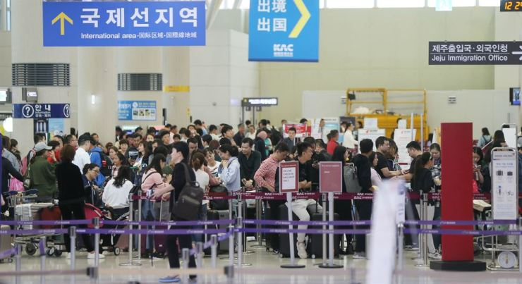 Tourists returning home gather at a waiting room at the Jeju International Airport Saturday afternoon as airlines have started resuming flight operations after Typhoon Kong-rey passed through the island. Yonhap