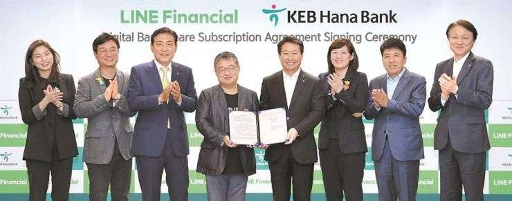 LINE Financial Asia CEO Hwang In-joon, fourth from left, and PT Bank KEB Hana Indonesia CEO Lee Hwa-soo show a signed agreement on a share subscription between the two entities at the group's headquarters in Seoul, Oct. 26. Third from left is Hana Financial Group CEO Kim Jung-tai. Courtesy of KEB Hana Bank