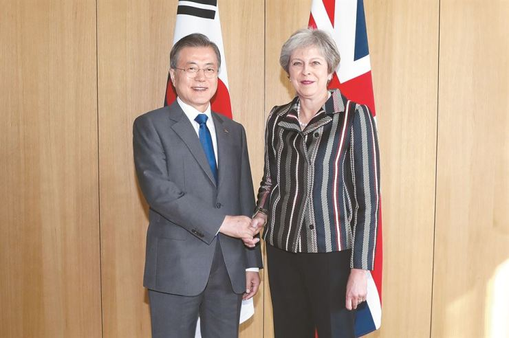 President Moon Jae-in shakes hands with British Prime Minister Theresa May during a meeting on the sidelines of an EU-ASEM summit in Brussels, Belgium, late Friday (KST).
