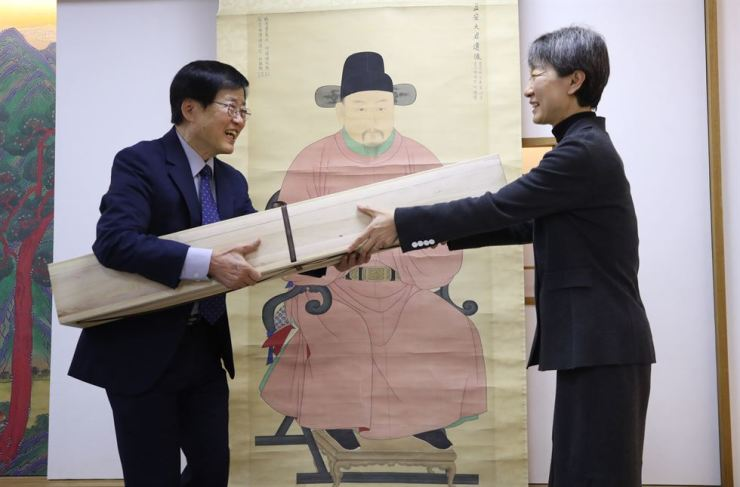 Cultural Heritage Administrator Chung Jae-suk, right, hands over the stolen portrait of Grand Prince Ikan to Yi Seok-hee of the Jeonju Yi clan during a returning ceremony at the National Palace Museum of Korea, Tuesday. Yonhap