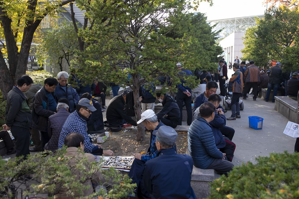 A group of old men play janggi, or Korean chess, outside the northern walls of Tapgol Park in central Seoul, Oct. 25. / Korea Times photo by Shim Hyun-chul