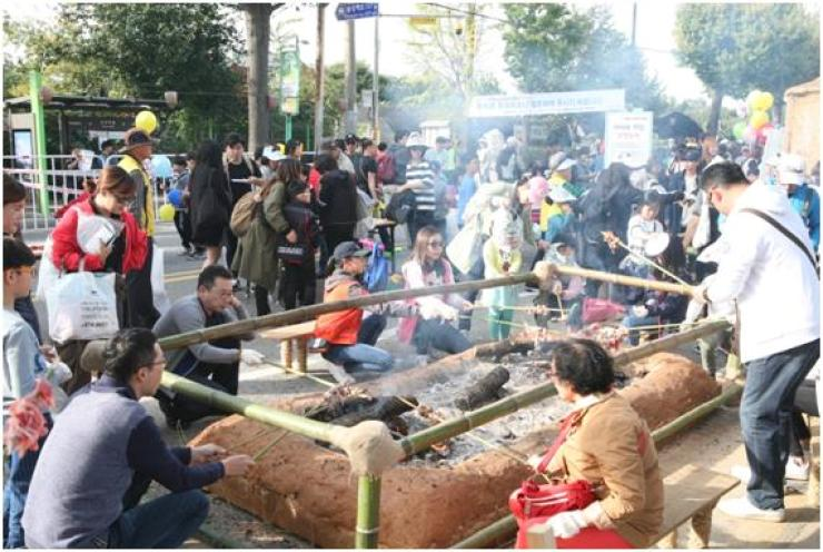 People cook barbecue like prehistoric times at Amsa-dong Prehistoric Settlement Site during last year's Prehistoric Culture Festival in Gangdong-gu, eastern Seoul. This year's festival is being held from Oct. 12 to 14./ Courtesy of Gangdong-gu Office.