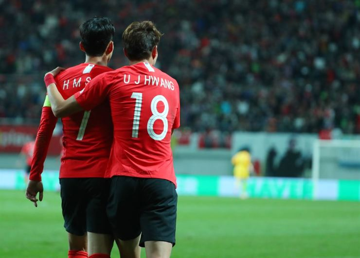 Son Heung-min, left, celebrates with teammate Hwang Ui-jo after Hwang's first goal during the international friendly match between South Korea and Uruguay at the Seoul World Cup Stadium in Seoul, Friday. Yonhap