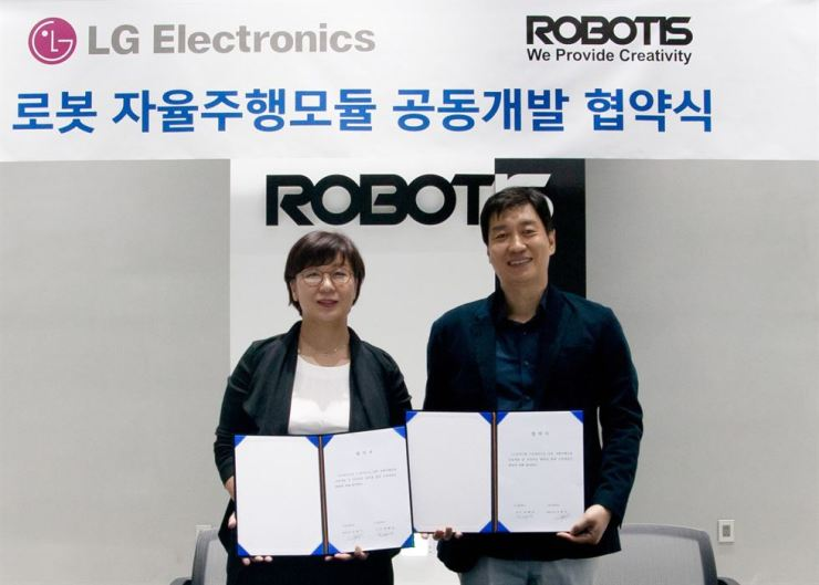 Ryu Hye-jung, left, head of smart solution business division of LG Electronics' Home Appliance & Air Solutions Company, poses with Robotis CEO Kim Byoung-soo after signing a contract to develop self-driving modules for robots, at Robotis' headquarters in Magok-dong, western Seoul, Sept. 28. / Courtesy of LG Electronics