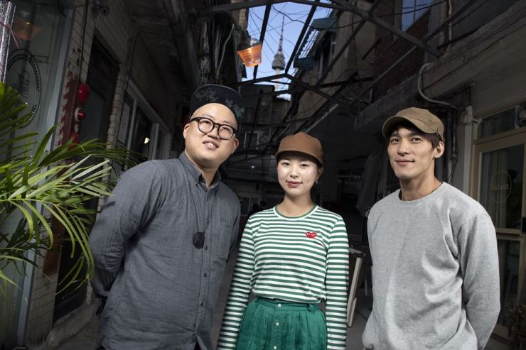 Young tenants pose for a photo at Sinheung Market in Haebangchon, central Seoul, Monday. From left are leather craftsman Park Ki-dong, jewelry designer Kim Sae-rom and cafe owner Jang Kyung-Hoon. / Korea Times photo by Choi Won-suk