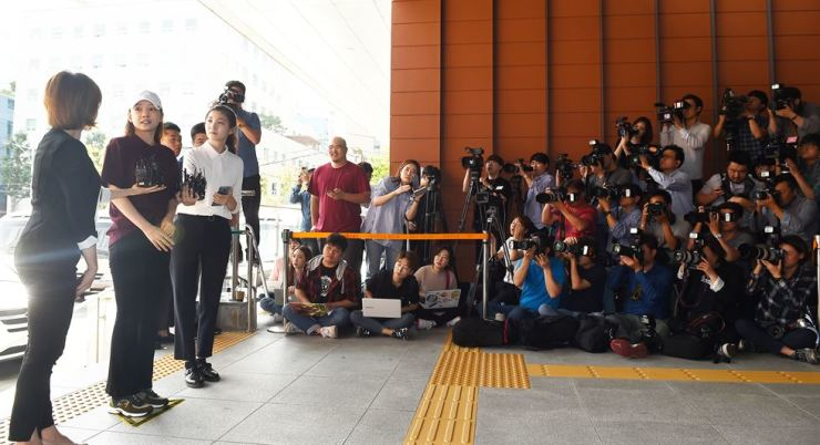 K-pop star Koo Ha-ra talks to reporters outside Gangnam Police Station, southern Seoul, Sept. 18. / Korea Times file