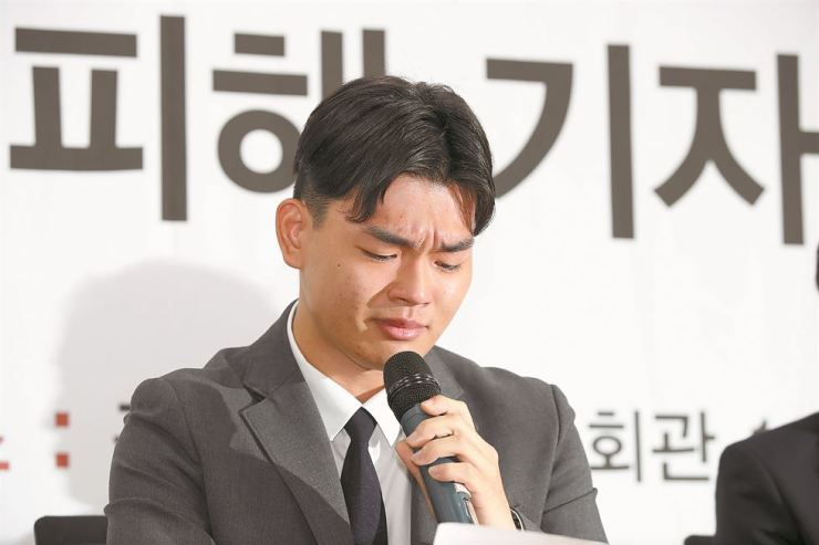 Lee Seok-cheol, a former member of the K-pop group The East Light, sheds tears while testifying in Seoul, Friday, about alleged assaults and threats he and his brother suffered at the hands of Media Line Entertainment producer Moon Young-il. The Lee brothers were forced to leave the agency after they made the abuse allegations public. Yonhap