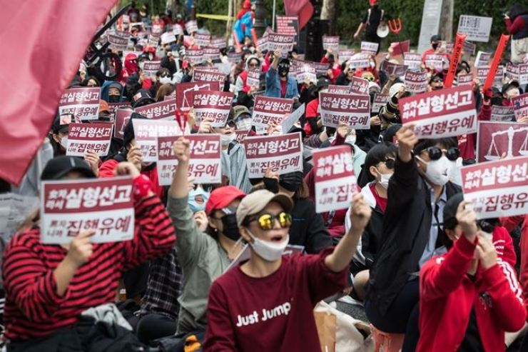 Protestors chant slogans near Hyehwa Station in Seoul, Saturday against Korea's judiciary system, which they believe favors men in spycam cases. / Korea Times file