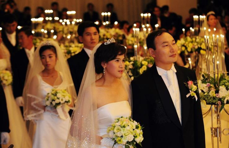 Twenty-two cross-border couples walk down the aisle in a joint wedding ceremony hosted by Rotary International at Heritz Wedding Convention Tower in southern Seoul, Oct. 4, 2010. The Korean grooms married brides from Cambodia, Vietnam, the Philippines and China. Korea Times