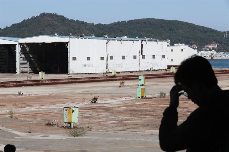 A man in silhouette stands in front of a bankrupt shipbuilder in Tongyeong, South Gyeongsang Province. More than 5,000 lost their jobs following its collapse in 2015. Yonhap