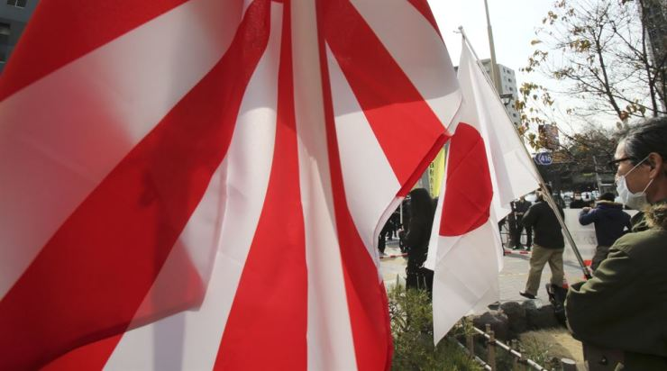 In this Feb. 22, 2013, file photo, a Japanese protester holds the rising sun flag and Japanese flag during a rally against South Korea in Tokyo.
