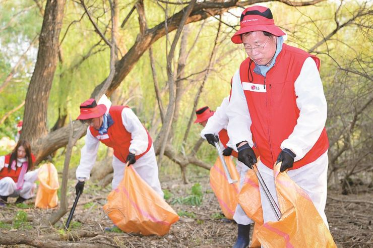 LG Chem Vice Chairman Park Jin-soo, right, participates in the cleanup event along with the firm's employees on Bamseom, an island in the Han River, Monday. LG Chem employees have been volunteering as the island's keepers since last year. / Courtesy of LG Chem
