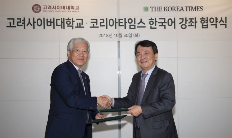Cyber University of Korea President Kim Jin-sung, left, and President and Publisher of The Korea Times Lee Byeong-eon shake hands during the memorandum of understanding signing ceremony at the newspaper company's building in central Seoul, Tuesday. / Korea Times photo by Choi Won-suk