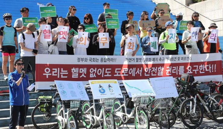 Members of 10 bike communities hold a rally against the revised traffic law mandating riders wear helmets, in front of the Sejong Center for the Performing Arts in Seoul, Saturday. / Yonhap