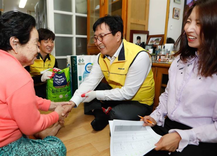 Daelim Industrial CEO Pak Sang-shin shakes hands with a resident of Muak-dong, Seoul, during a charity event offering rice and toilet paper to residents of the area, Wednesday. To commemorate the company's 79th anniversary, Pak and 100 other Daelim Industrial employees provided the gifts to socially vulnerable households in the area. / Courtesy of Daelim Industrial