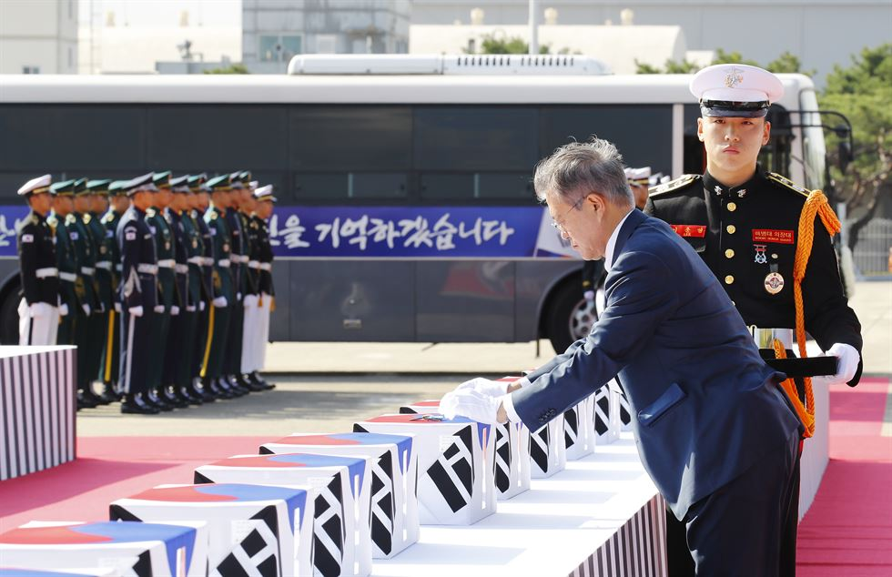 President Moon Jae-in, center, top military brass and war veterans salute to the war remains during the repatriation ceremony at Seoul Air Base in Seongnam, Monday. / Yonhap