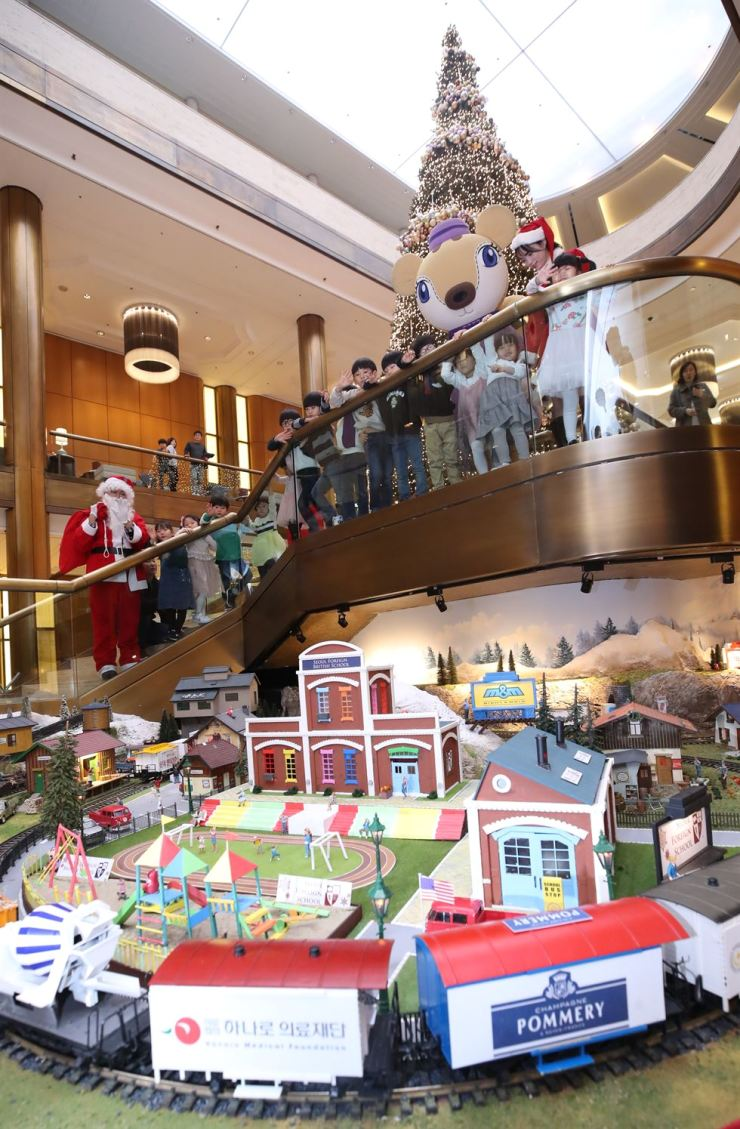Children watch the Millennium Seoul Hilton Christmas train display at the hotel in central Seoul, Sunday. Composed of 70 miniature trains, the 23rd annual Christmas decorations will be available to the public until Jan. 20. / Yonhap