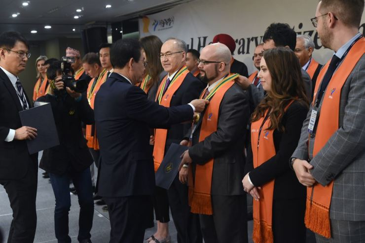 Seoul Mayor Park Won-soon puts an honorary citizenship medal around the neck of Ryan Goessl, executive/artistic director of Camarata Music Company.