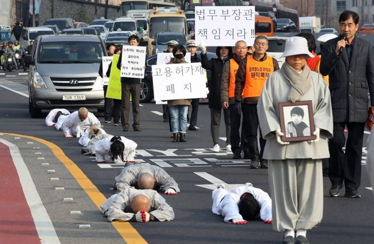 Monks and other members of the Jogye Order of Korean Buddhism prostrate on roads near the Jogyesa in Jongno-gu, Seoul, Monday. They were protesting after a migrant worker from Myanmar died in hospital after falling while fleeing an Incheon immigration inspector at a construction site in Gimpo in August. The protesters hold pickets that read 'Hold the Justice Minister Responsible' and 'Abolish Employment Permit System.' Yonhap
