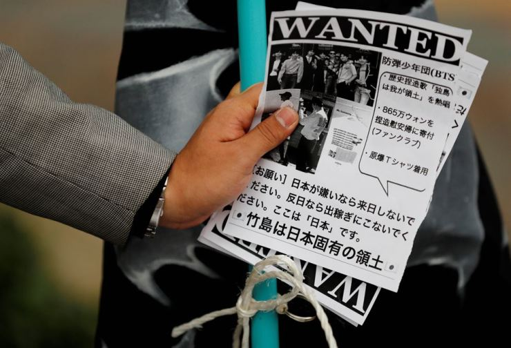 A man holds leaflets denouncing South Korean boy band BTS outside Tokyo Dome, where the band's concert was held, on Nov. 13. Reuters